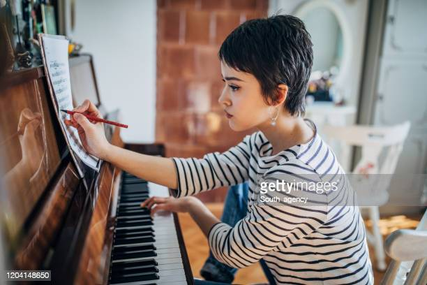 young woman pianist composing music in her room at home - keyboard player stock pictures, royalty-free photos & images