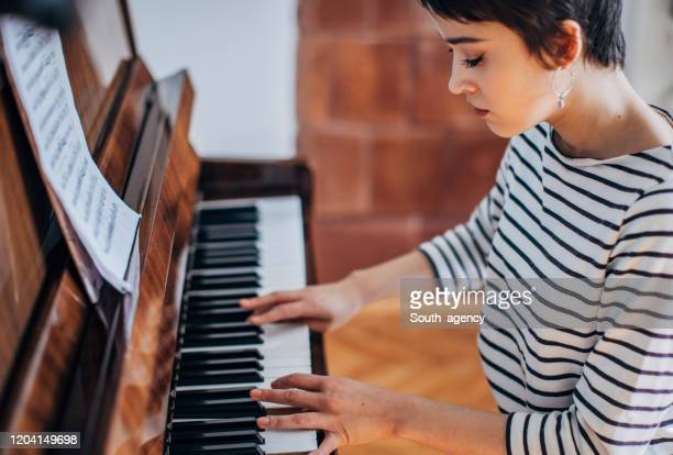 young woman pianist playing piano in her room at home - rehearsal stock pictures, royalty-free photos & images