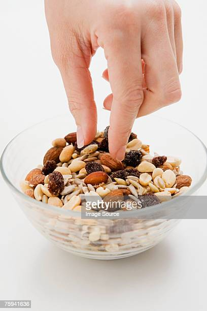 Young woman picking at a bowl of nuts