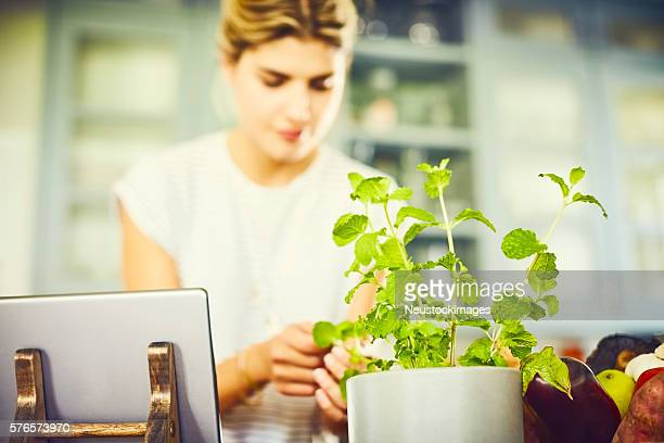Young woman picking mint leaves by digital tablet in kitchen