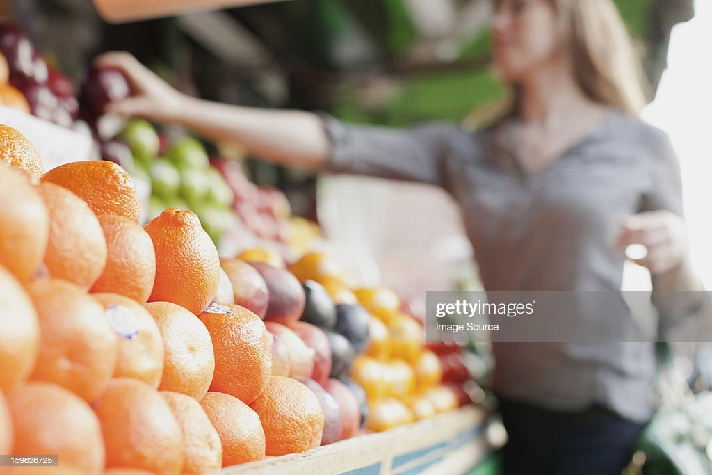 Young woman picking out fruit from stall : Stock Photo