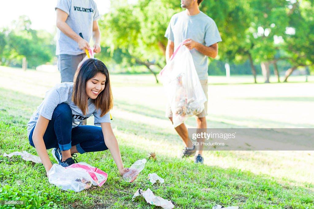 Giovane donna sceglie la spazzatura nel parco : Foto stock