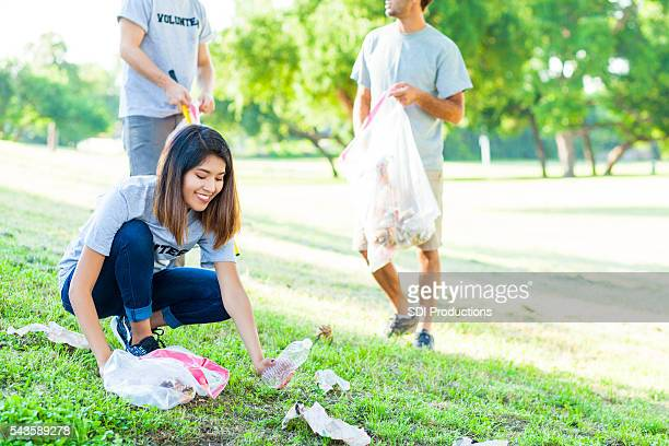 Young woman picks up trash in park