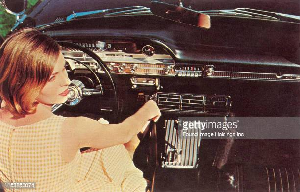 Young woman pictured from behind, sits at the wheel of a car.