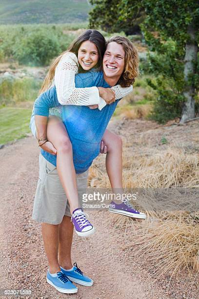 Young woman piggy back riding on her boyfriend