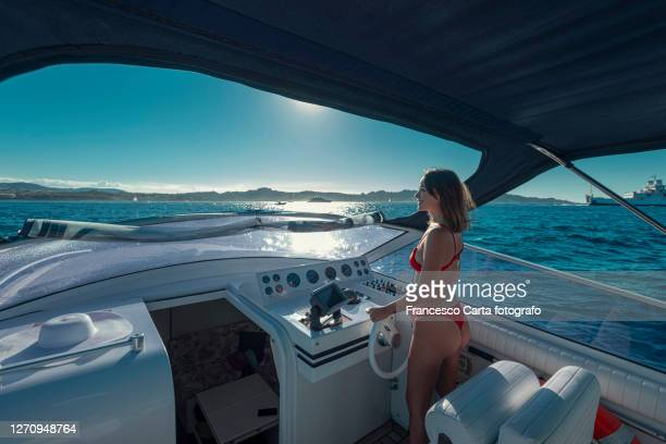 young woman piloting a motorboat - three quarter length stock pictures, royalty-free photos & images