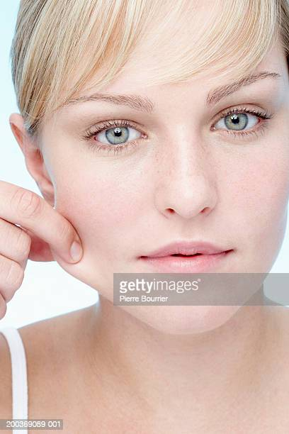 Young woman pinching cheek, portrait, close-up