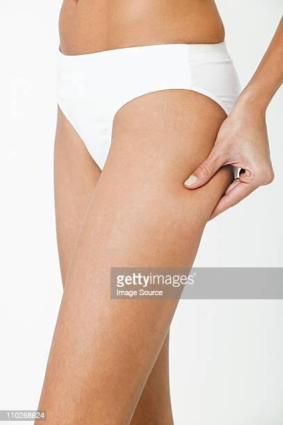 Young woman pinching thigh