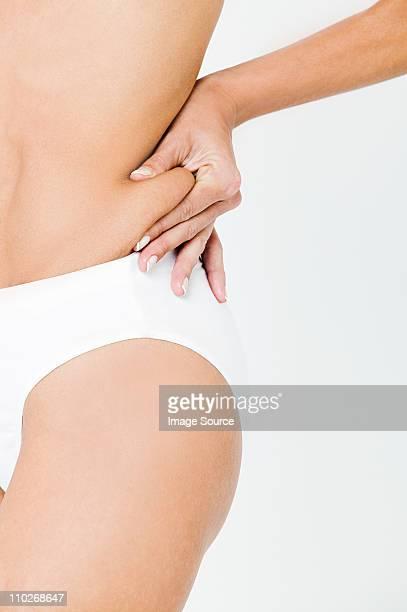 Young woman pinching waist