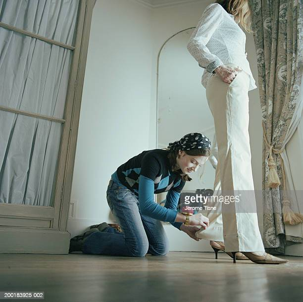 Young woman pinning hem on woman's trousers
