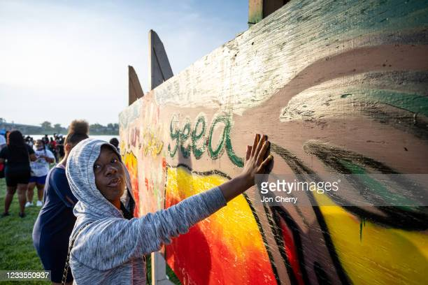 Young woman places her painted handprint on a piece of art created during the Louisville Juneteenth Festival at the Big Four Lawn on June 19, 2021 in...