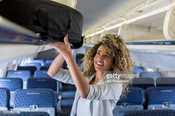 young woman places luggage in overhead bin on airplane - luggage stock pictures, royalty-free photos & images