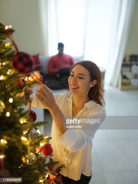 young woman placing a christmas ornament on a christmas tree - mexican christmas stock pictures, royalty-free photos & images