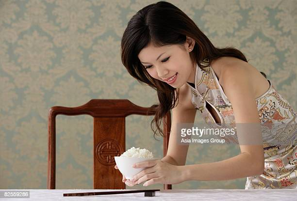 young woman placing bowl of rice on table - bend over woman stock pictures, royalty-free photos & images