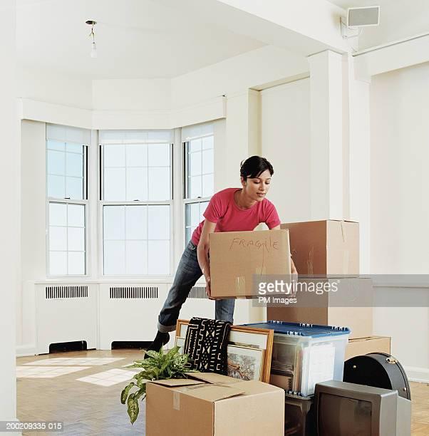 young woman placing box on stack of belongings in apartment - movilidad fotografías e imágenes de stock
