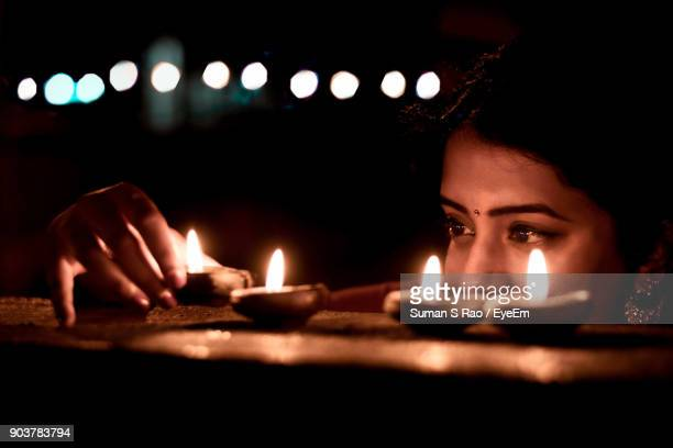 young woman placing diya on retaining wall at night - diwali celebration stock photos and pictures