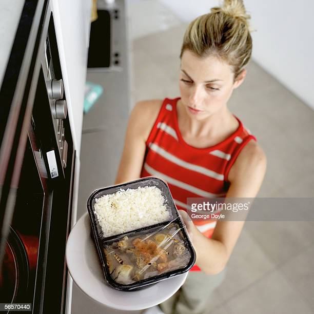 young woman placing food in the microwave - cibo pronto foto e immagini stock