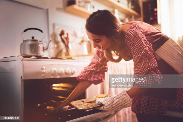 young woman placing pies in kitchen oven for baking - old fashioned thanksgiving stock photos and pictures
