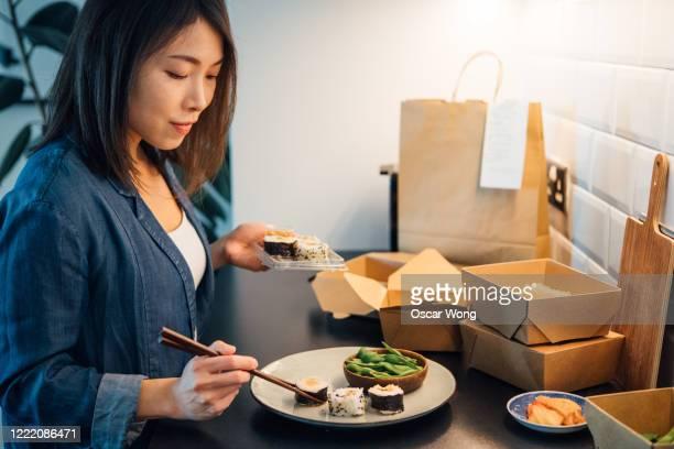 young woman placing takeaway sushi on plate - prato de soja - fotografias e filmes do acervo