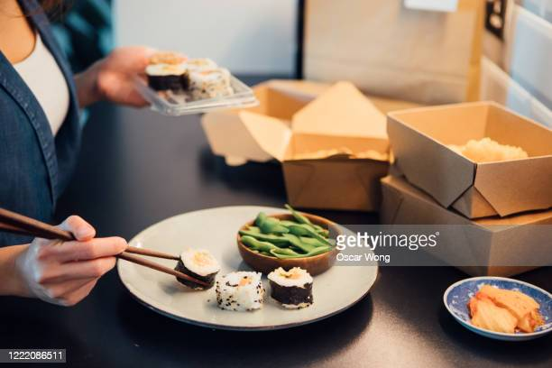 young woman placing takeaway sushi on plate - take away food stock pictures, royalty-free photos & images