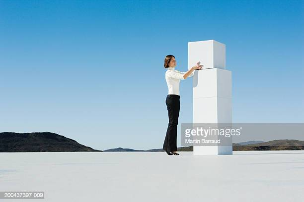 Young woman placing white cube on top of stacked white cubes
