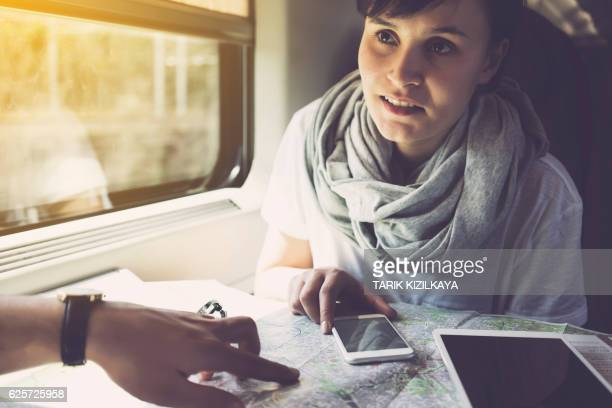 Young woman planning a trip, using smartphone, travelling by train
