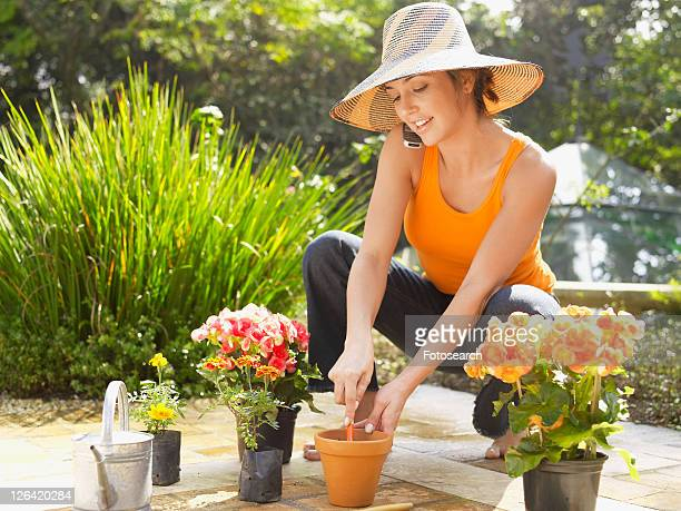 Young woman planting flowers and talking on cell phone