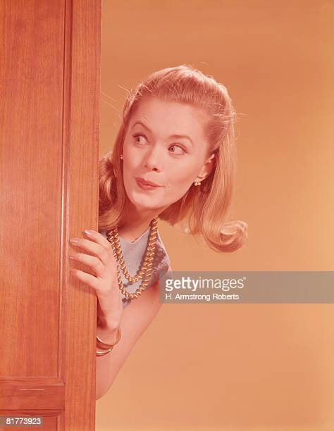 Young woman playfully peeking around door. (Photo by H. Armstrong Roberts/Retrofile/Getty Images)