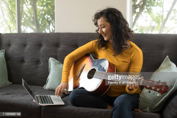 young woman playing a guitar in her home - musical instrument stock pictures, royalty-free photos & images