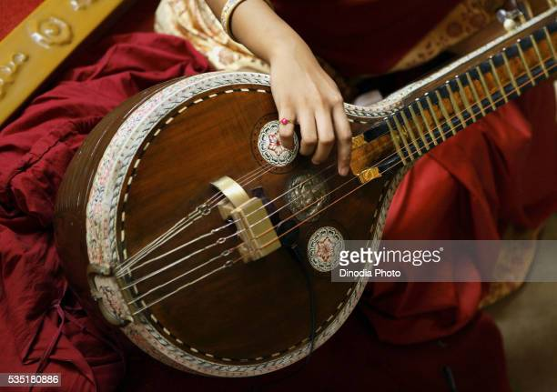 Young woman playing a South Indian musical instrument called a veena during a religious ceremony.