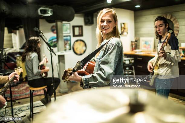 young woman playing acoustic guitar at band rehearsal - guitarist stock pictures, royalty-free photos & images