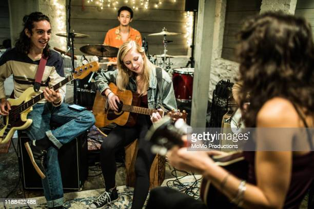 young woman playing acoustic guitar at band rehearsal - guitar stock pictures, royalty-free photos & images