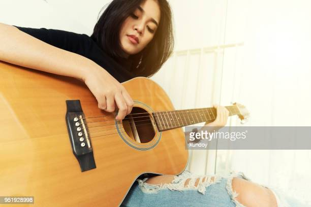 young woman playing acoustic guitar at home. music and relaxing times. - acoustic music stock pictures, royalty-free photos & images