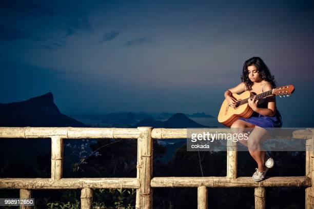 Young woman playing acoustic guitar in Rio de Janeiro