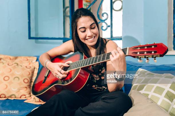 young woman playing acoustic guitar - plucking an instrument stock pictures, royalty-free photos & images
