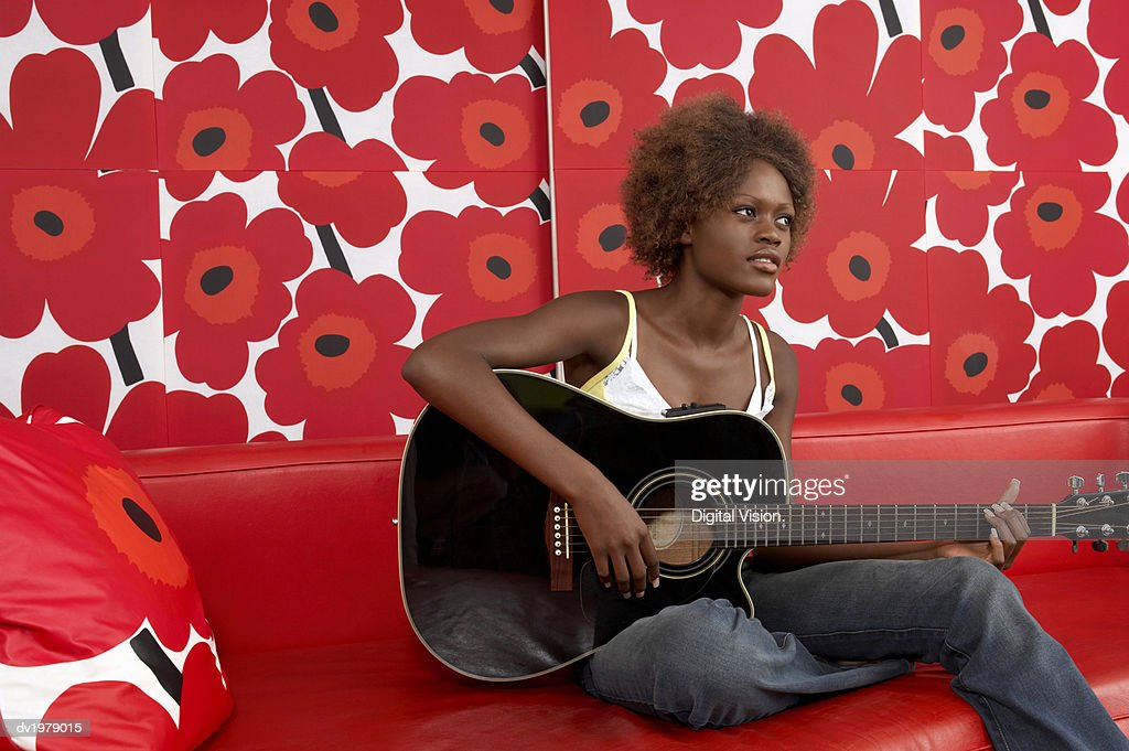 Young Woman Playing an Acoustic Guitar on a Red Leather Sofa Against Floral Wallpaper : Stock Photo