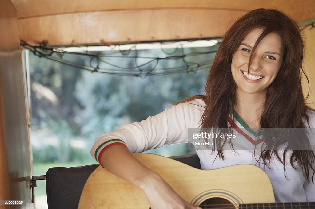 Young Woman Playing an Acoustic Guitar on the Back Seat of a Motor Home : Stock Photo