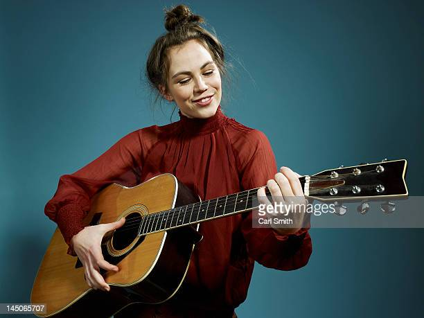 a young woman playing an acoustic guitar - acoustic guitar stock pictures, royalty-free photos & images