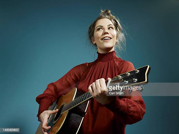 a young woman playing an acoustic guitar - looking down her blouse stock photos and pictures