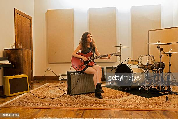 young woman playing an electric guitar - chanteur photos et images de collection