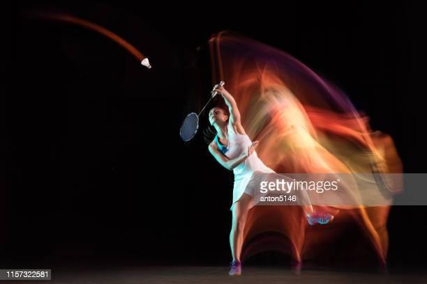 黒いスタジオの背景に孤立したバドミントンをする若い女性 - スポーツ バドミントン ストックフォトと画像