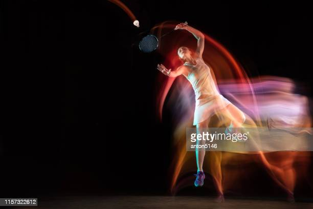 young woman playing badminton isolated on black studio background - badminton sport stock pictures, royalty-free photos & images