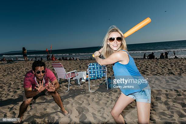 Young woman playing baseball on beach, Santa Monica, California, USA