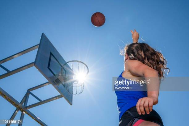 young woman playing basketball, against the sun - making a basket scoring stock photos and pictures