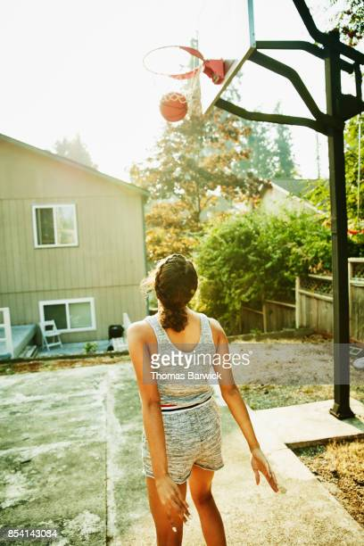 Young woman playing basketball in backyard on summer afternoon