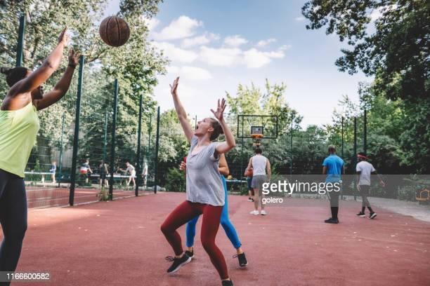 junge frau spielt basketball auf dem hartplatz - mannschaftssport stock-fotos und bilder