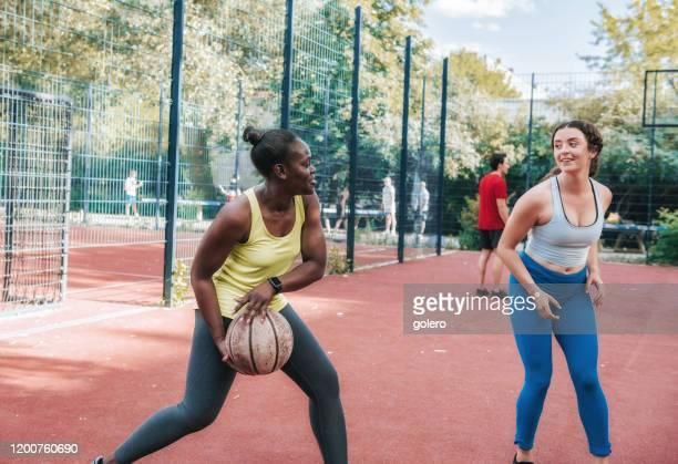 jeune femme jouant au basket-ball sur le dur - sport d'équipe photos et images de collection