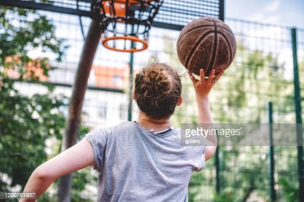 joven jugando baloncesto en la cancha dura - atleta papel social fotografías e imágenes de stock