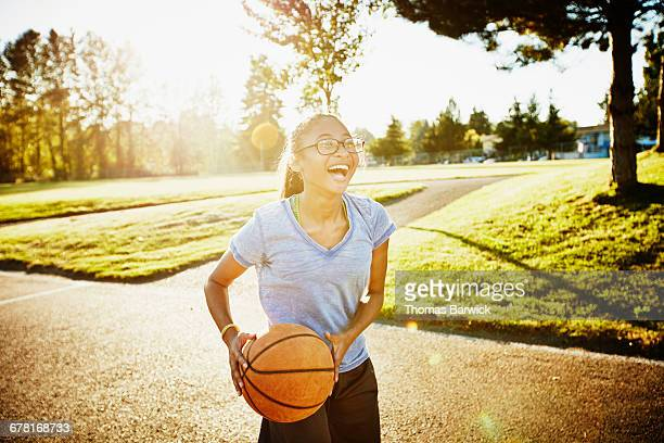 Young woman playing basketball on outdoor court