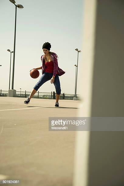 Young woman playing basketball outdoors